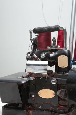 threaded: Old industrial overlocking machine in sewing factory with red thread