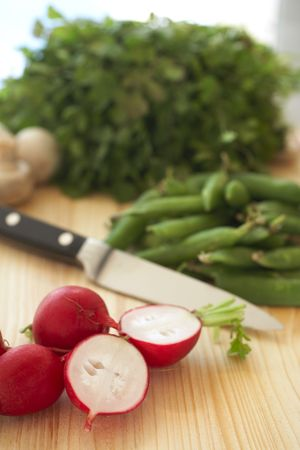 A variety of vegetables on a wooden cutting board, including parsley, radish, beans and mushrooms Stock Photo - 2619247