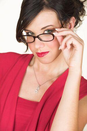 rimmed: J�venes adultos morena de negocios con cuerno rimmed gafas y un vestido rojo. Ella es de raza cauc�sica y usa l�piz de labios rojo brillante. No aislado