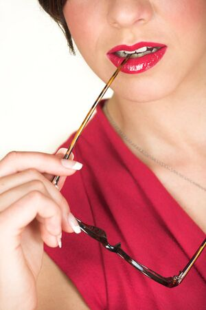 Young adult brunette businesswoman biting her horn rimmed glasses and a red dress. She is Caucasian and wears bright red lipstick. White background, not Isolated photo