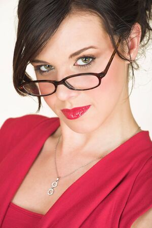 rimmed: Young adult brunette businesswoman with horn rimmed glasses and a red dress. She is Caucasian and wears bright red lipstick.