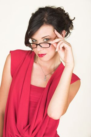 rimmed: Young adult brunette businesswoman with horn rimmed glasses and a red dress. She is Caucasian and wears bright red lipstick. NOT ISOLATED