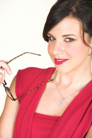 rimmed: Young adult brunette businesswoman with horn rimmed glasses and a red dress. She is Caucasian and wears bright red lipstick. White background, not Isolated