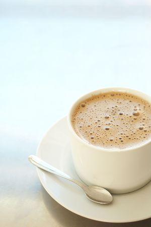 tomando leche: Fresh espumoso caf� latte en blanco taza de caf� sobre un fondo de plata con un mont�n de espacio � copia profundidad de campo, se centran en la espuma