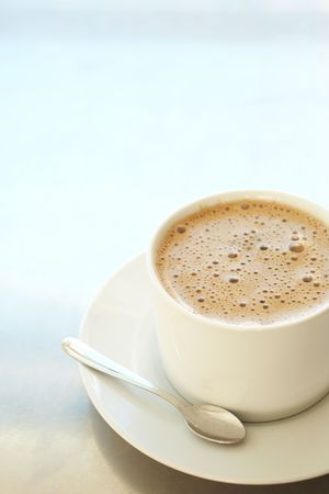 Fresh foamy cafe latte in white coffee cup on a silver background with lots of copy space � Shallow Depth of Field, focus on Foam Stock Photo