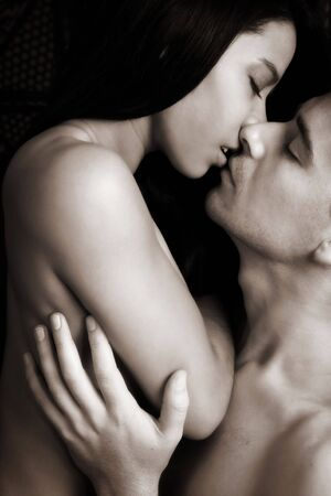 Multi-ethnic couple in passionate embrace and undressing each other during ual foreplay - High Contrast Black and White Stock Photo - 2796423
