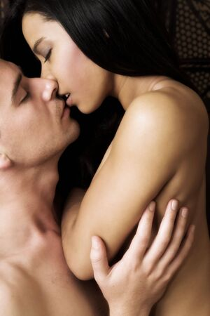 Multi-ethnic couple in passionate embrace and undressing each other during ual foreplay