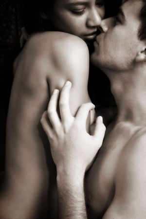 Multi-ethnic couple in passionate embrace and undressing each other during ual foreplay. High Contrast Black and White - Defocussed
