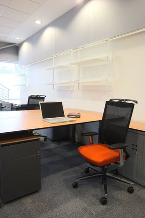 ofis koltuğu: Empty office with new modern office furniture, including desks, cupboards, filing cabinets and chairs. With a notebook computer on the desk. HDR type image