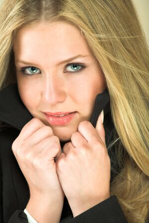 Portrait of a beautiful young adult Caucasian woman with light skin and straight blond hair, green eyes and red lips, wearing a white shirt and black flannel winter coat photo