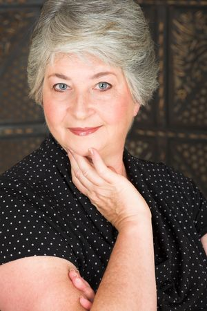 Beatiful older caucasian woman in black blouse, with blue-grey eyes and silver hair.