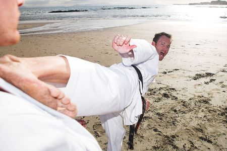sensei: Young adult men practicing Karate on the beach. One is in a high kick on the chest of the other (some movement on the edges) Stock Photo