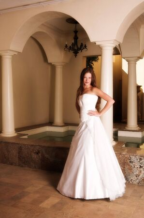 Slim beautiful adult woman with long brown, curly hair wearing luxurious silk wedding dress on location Stock Photo - 2871180