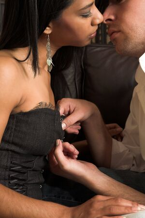 Multi-ethnic couple in passionate embrace and undressing each other during sexual foreplay Stock Photo