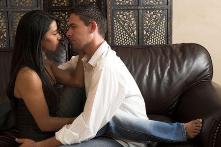 Los pares multi-ethnic en apasionado abrazan y desnudándose durante foreplay sexual