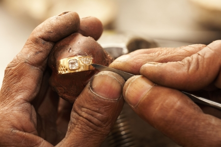 Goldsmith working on an unfinished 22 carat gold ring with his hard working hands. Half of the Diamonds already embedded.