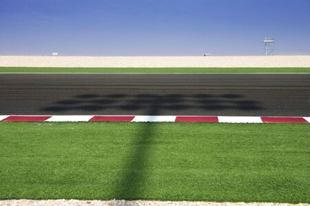 lighting system: Section of  asphalt next to  race track. Shadow from lighting system running over track.