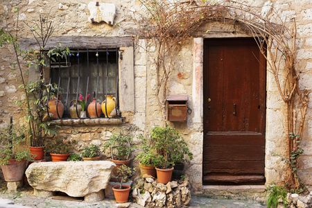 Street garden with Street name and potted plants in front of windows and doors in the quaint little French hilltop village of Saint-Paul de Vence, Southern France,  Alpes Maritimes, next to the Mediterranean sea - a Heritage Site Stock Photo