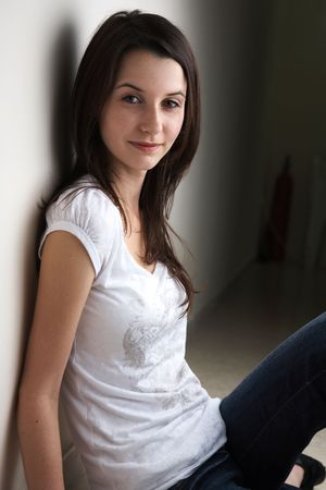 light brown eyes: Portrait of a beautiful young adult (teenager) Caucasian woman with light skin and dark brown hair, brown eyes and pink lips, sitting against a wall