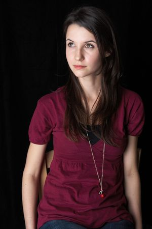 dark brown hair: Portrait of a beautiful young adult (teenager) Caucasian woman with light skin and dark brown hair, brown eyes and pink lips, sitting against a black background (not isolated)