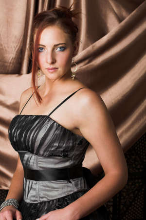 Beautiful young sexy adult Redheaded woman with long auburn hair, in formal black dress on a textured silk background � Hard light, high key Stock Photo - 2871283