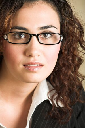 light brown eyes: Portrait of a beautiful young adult Caucasian businesswoman with light skin and curly brown hair, brown eyes and pink lips, wearing a pinstripe Jacket and white shirt with spectacles