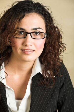 cabello casta�o claro: Retrato de una hermosa joven empresaria de adultos de raza cauc�sica con luz piel y el cabello rizado casta�o, ojos marrones y rosados labios, el uso de una pinstripe Chaqueta y camisa blanca con gafas