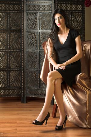 Beautiful young sexy adult Italian woman with long black hair, in formal black dress on a textured wooden background, sitting on a luxurious couch Ð Hard light, high key