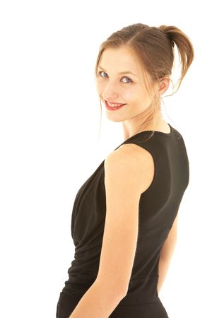 Sexy young adult Caucasian businesswoman in a formal black dress on a white background, looking over her shoulder. Not isolated photo