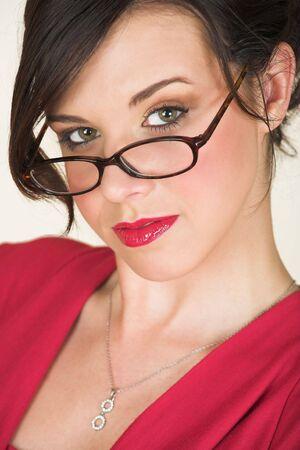 rimmed: J�venes adultos morena de negocios con cuerno rimmed gafas y un vestido rojo. Ella es de raza cauc�sica y usa l�piz de labios rojo brillante.