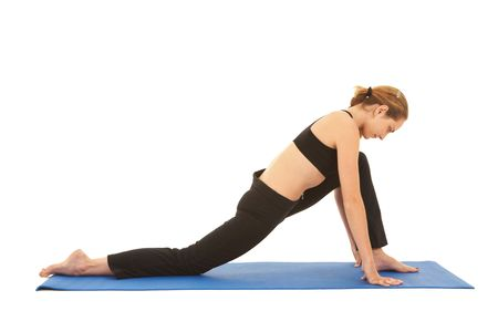 Fit young brunette pilates instructor showing different exercises on a white background a blue yoga mat. Stock Photo