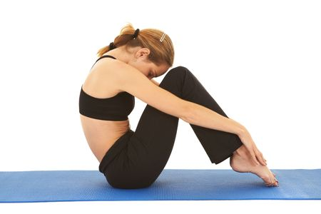 muscle toning: Fit young brunette pilates instructor showing different exercises on a white background a blue yoga mat. Stock Photo