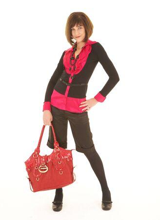 leren tas: Zaken sexy jonge volwassen blanke vrouw in een rode en zwarte bedrijfs uitrusting tegen een witte achtergrond met een rood lederen tas. NIET GEÏSOLEERD