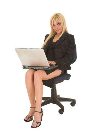 Sexy young adult Caucasian businesswoman in black pinstripe pencil skirt and suit jacket on a white background, sitting on an office chair with a notebook computer