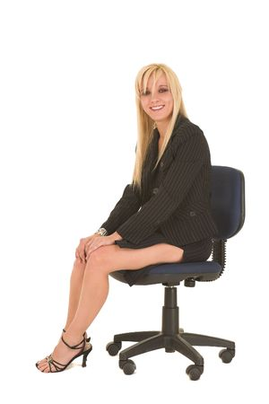 skirt suit: Sexy young adult Caucasian businesswoman in black pinstripe pencil skirt and suit jacket on a white background, sitting on an office chair Stock Photo