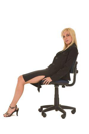 slit: Sexy adultos j�venes de raza cauc�sica de negocios en negro pinstripe falda l�piz y chaqueta de traje sobre un fondo blanco, sentado en una silla de oficina