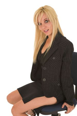 pencil skirt: Sexy young adult Caucasian businesswoman in black pinstripe pencil skirt and suit jacket on a white background, sitting on an office chair Stock Photo