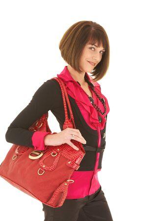 leren tas: Sexy jonge volwassen blanke zakenvrouw in een rode en zwarte kantoor outfit tegen een witte achtergrond met een rode lederen tas. NIET ISOLATED Stockfoto