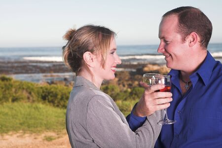 Young adult Caucasian couple drinking wine outdoor next to the ocean Stock Photo - 3129787