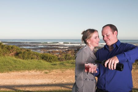 Young adult Caucasian couple drinking wine outdoor next to the ocean Stock Photo - 3129785