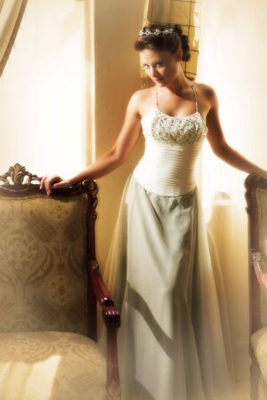 Slim beautiful adult woman with long brown, curly hair wearing luxurious silk wedding dress on location. Defocused, dreamy effect Stock Photo - 3200589
