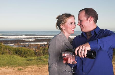 Young adult Caucasian couple drinking wine outdoor next to the ocean Stock Photo - 3171478