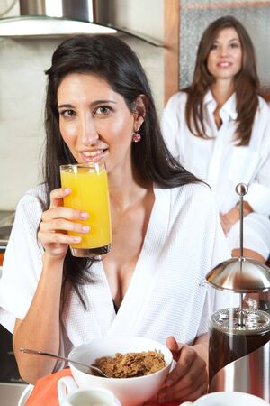 Sexy young adult brunette roommates in lingerie eating breakfast and drinking coffee in their kitchen before work Stock Photo - 3171452