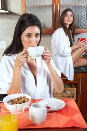 Sexy young adult brunette roommates in lingerie eating breakfast and drinking coffee in their kitchen before work Stock Photo - 3171447