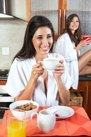 Sexy young adult brunette roommates in lingerie eating breakfast and drinking coffee in their kitchen before work Stock Photo - 3171450