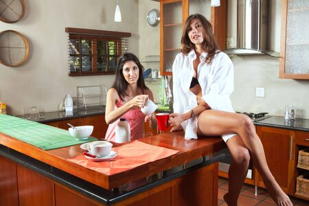 Sexy young adult brunette roommates in lingerie eating breakfast and drinking coffee in their kitchen before work. Girl sitting on counter Stock Photo - 3171466