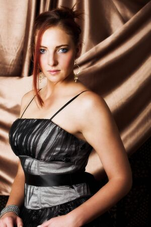 auburn hair: Beautiful young sexy adult Redheaded woman with long auburn hair, in formal black dress on a textured silk background Ð Hard light, high key. Defucussed