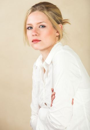 Portrait of a beautiful young adult Caucasian woman with light skin and straight blond hair, green eyes and red lips, wearing a white shirt photo