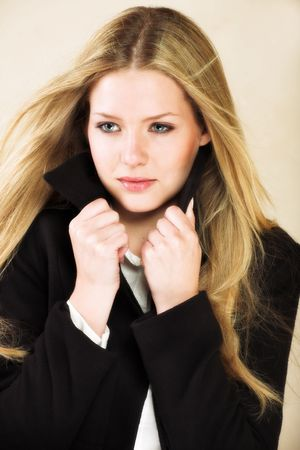 flannel: Portrait of a beautiful young adult Caucasian woman with light skin and straight blond hair, green eyes and red lips, wearing a white shirt and black flannel winter coat