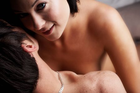 Young adult Caucasian couple in passionate embrace and undressing each other during sexual foreplay. The woman is wearing blue contact lenses Stock Photo - 3233421
